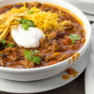 Crock-Pot Turkey Chili is made in the slow cooker with three beans, lean ground turkey, bell pepper, yellow onion, seasonings and tomatoes. Top with whatever goodies your family enjoys including sour cream, shredded cheddar cheese and tortilla strips | crockpot recipes | winter recipe | family friendly recipes | ground turkey | #chili
